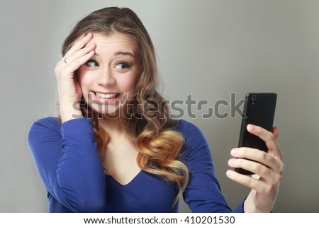 Closeup portrait anxious scared young girl looking at phone seeing bad news photos message with disgusting emotion on her face isolated on gray wall background. Human reaction - stock photo