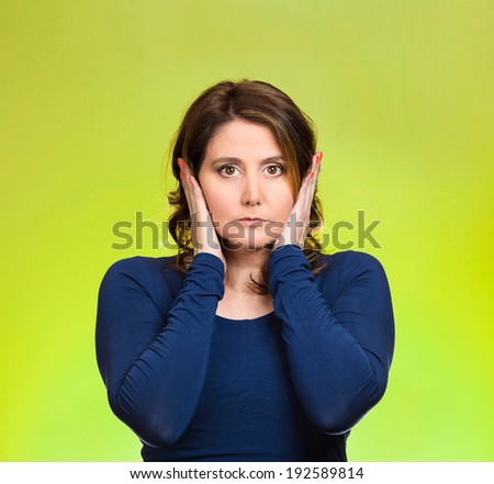 Closeup portrait attractive, calm, peaceful, looking relaxed young woman, covering ears, eyes open, isolated green background. Hear no evil concept. Human emotions, facial expression, attitude, mood - stock photo