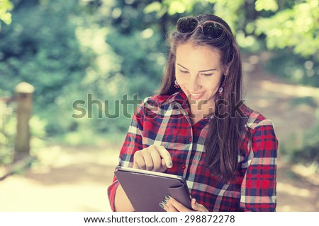 Closeup portrait attractive happy casual woman using pc isolated on park outdoors tree background. Positive human emotion feelings. Technology in modern life concept  - stock photo
