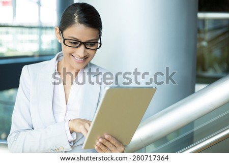 Closeup portrait, attractive happy woman in gray white suit and black glasses using silver pc, isolated indoors interior office background. Positive human emotion facial expressions feelings - stock photo