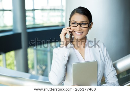 Closeup portrait, attractive happy woman in gray white suit and black glasses using silver pc and phone, isolated indoors interior office background. Positive human emotion facial expressions feelings - stock photo