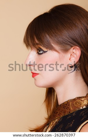 Closeup portrait attractive orient eastern girl with perfect make-up. Woman with beauty makeup eye liner red lips and tatoo near ear, face profile
