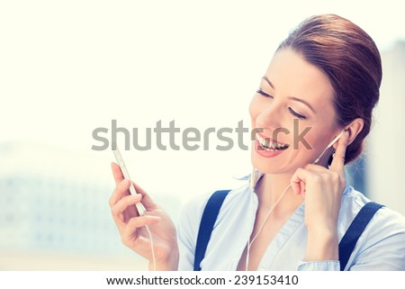 Closeup portrait attractive smiling business woman walking on street listening to music on mobile phone outdoors laughing isolated city background. Positive human emotion face expression. Urban life - stock photo