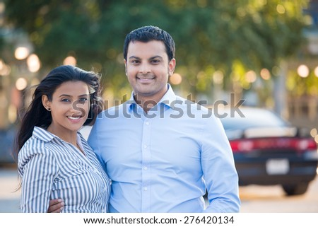 Closeup portrait, attractive wealthy successful couple in blue shirt and striped outfit holding each other smiling, isolated outside green trees and black car background.  - stock photo