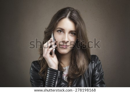 Closeup portrait attractive young girl at phone looking at camera on texture background. Human emotion, reaction, expression  - stock photo
