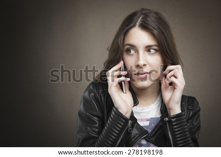 Closeup portrait attractive young girl at phone on texture background. Human emotion, reaction, expression  - stock photo
