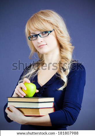 Closeup portrait attractive young happy smiling woman, student with glasses holding pile of text books, apple isolated dark blue background. Education college concept. Positive emotion face expression - stock photo