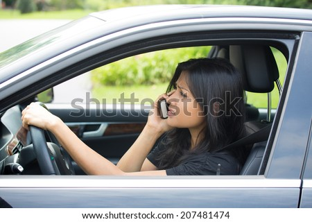 Closeup portrait, attractive young woman sitting, driving in black car on cellphone with bad news, isolated outdoors background - stock photo