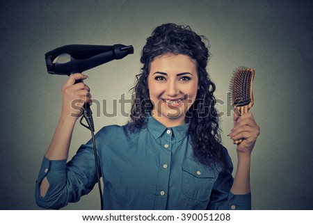 Closeup portrait beautiful happy young woman with the hair dryer and brush isolated on gray wall background  - stock photo