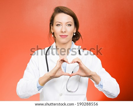Closeup portrait, beautiful smiling cheerful health care professional, pharmacist, dentist, nurse making heart sign hands, isolated red background. Positive human emotion facial expression feeling