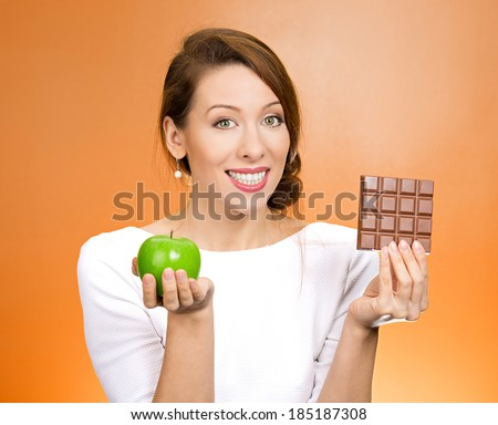 Closeup portrait, beautiful, smiling young woman offering nutritious lime apple as an alternative to unhealthy square milk chocolate, isolated orange background. Food diet option situations, dilemma. - stock photo