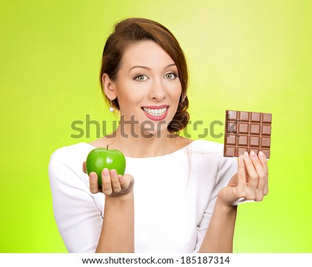 Closeup portrait, beautiful, smiling young woman offering nutritious lime apple as an alternative to unhealthy square milk chocolate, isolated green background. Food diet option situations, dilemma. - stock photo