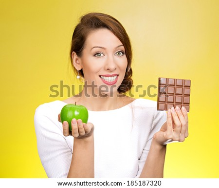 Closeup portrait, beautiful, smiling young woman offering nutritious lime apple as an alternative to unhealthy square milk chocolate, isolated yellow background. Food diet option situations, dilemma - stock photo