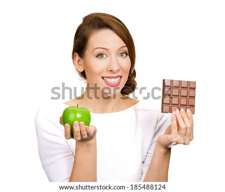 Closeup portrait, beautiful, smiling young woman offering nutritious lime apple as an alternative to unhealthy square milk chocolate isolated white background, clipping path. Food diet option dilemma. - stock photo