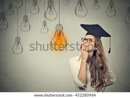 Closeup portrait beautiful thoughtful graduate student girl young woman in cap gown looking up at bright light bulb thinking isolated gray wall background. Graduation ceremony future career concept - stock photo