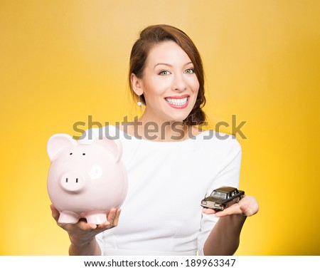 Closeup portrait, beautiful, young woman, dealership agent holding model black car, pink piggy bank in hand, offering credit line, isolated yellow background. Lease, automobile purchase, financing.