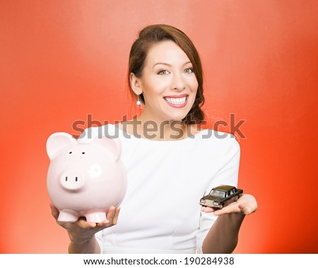 Closeup portrait, beautiful, young woman, dealership agent holding model black car, pink piggy bank in hand, offering credit line, isolated red background. Lease, automobile purchase, financing.