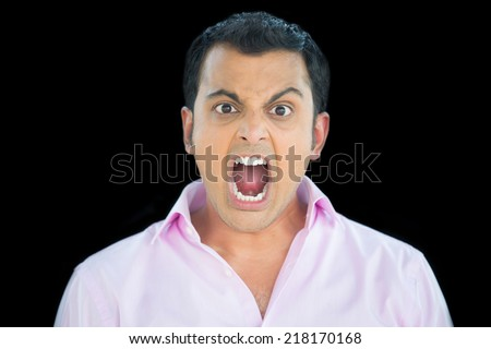 Closeup portrait, bitter, displeased pissed off, angry grumpy man in pink shirt, open mouth, screaming and yelling, isolated black background. - stock photo