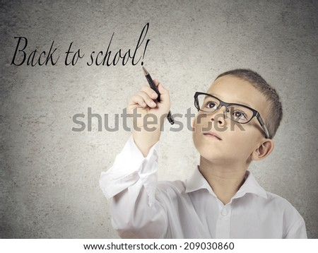 Closeup portrait boy, little man, student writing with pen back to school, isolated grey wall background. Education, knowledge concept. Face expressions - stock photo