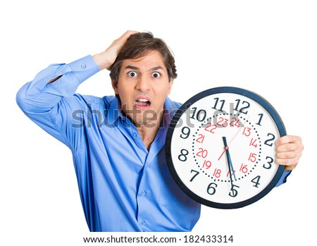 Closeup portrait business man, worker, guy holding clock looking anxiously, pressured by lack, running out of time isolated white background. Human face expression, emotion, reaction, corporate life