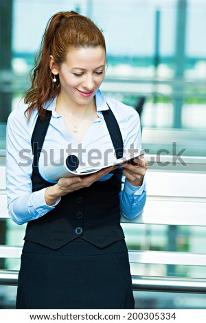 Closeup portrait business woman, editor reading latest news in magazine, smiling happy, great news article, ideas isolated background corporate office windows. Positive human facial expression emotion - stock photo