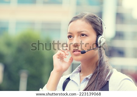 Closeup portrait business woman, serious customer service representative call centre worker operator, support staff speaking with head set listening client problem isolated background corporate office - stock photo