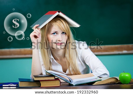 Closeup portrait business woman, student, teacher seating at desk thinking how to make money looking worried isolated green chalkboard background, bubble filled dollar signs. Facial expression emotion - stock photo
