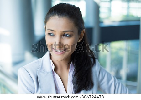 Closeup portrait, charming upbeat smiling joyful happy young woman looking side and down daydreaming something nice, isolated indoors office background. Positive human facial expressions feelings - stock photo