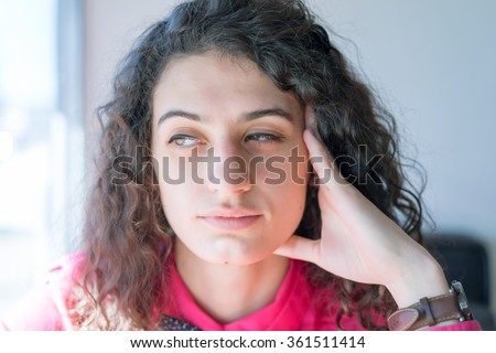 Closeup portrait, charming upbeat smiling joyful happy young woman looking side and down daydreaming something nice, isolated indoors background. - stock photo
