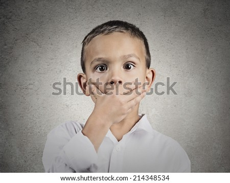 Closeup portrait child astonished face expression, covering mouth with hand, wide open eyes, isolated grey wall background. Human emotions, body language, perception. Unexpected discovery, reaction - stock photo