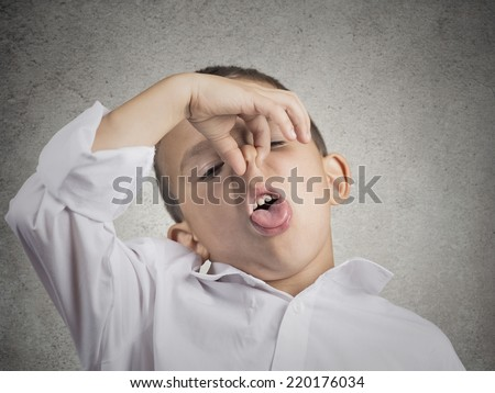 Closeup portrait child boy with disgust on face pinches his nose something stinks bad smell situation isolated grey wall background. Negative human emotions facial expressions perception body language - stock photo