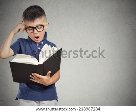 closeup portrait child with glasses reading book, isolated grey wall background with copy space. Human face expressions. Education concept - stock photo