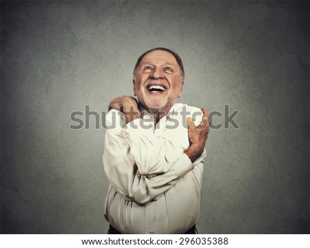 Closeup portrait confident smiling man holding hugging himself isolated on grey wall background. Positive human emotion, facial expression, feeling, reaction, attitude. Love yourself concept - stock photo