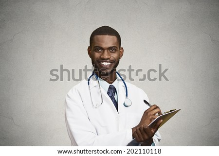 Closeup portrait, confident, smiling young male family doctor, cardiologist, health care professional taking notes from patient, isolated black, grey background. Positive human emotion face expression - stock photo