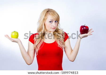 Closeup portrait confused, puzzled, unhappy, thoughtful young woman, girl, holding red, green apples, uncertain which one to chose. Human face expressions, emotion, reaction, attitude, life perception