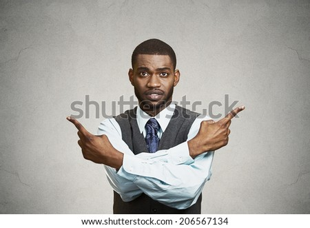 Closeup portrait confused young business man pointing in two different directions, not sure which way to go life, hesitant to make decision isolate black background. Emotion, facial expression feeling - stock photo