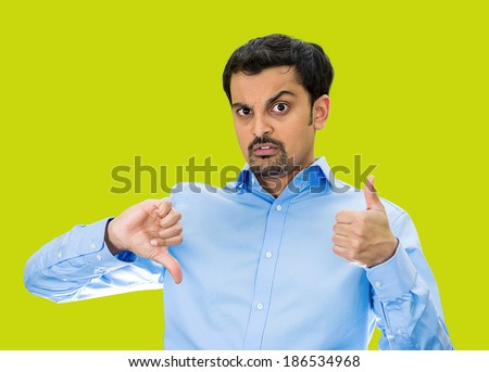 Closeup portrait, confused, young man pointing in two different directions, not sure if good or bad, showing thumbs up, down simultaneously, isolated green background. Emotion, face expression - stock photo