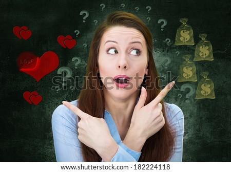 Closeup portrait confused young woman pointing in two different directions, not sure which way to go in life, isolated green background with dollar signs, red hearts. Emotion facial expression feeling - stock photo