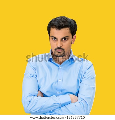Closeup portrait, displeased, angry, grumpy business man, bad attitude, arms crossed, folded, looking at you, isolated yellow background. Negative human emotion, facial expression, feeling - stock photo