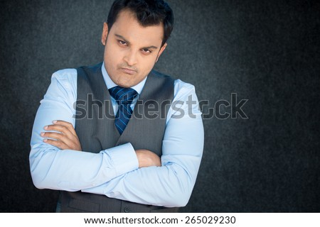Closeup portrait, displeased, angry, grumpy business man, bad attitude, arms crossed, folded, looking at you, isolated gray black background. Negative human emotion, facial expression, feeling - stock photo