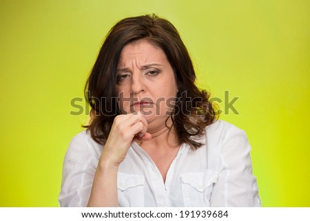 Closeup portrait displeased, pissed off, angry, grumpy, middle aged woman with bad attitude, hand on chin looking at you, isolated green background . Negative human emotion facial expression feeling - stock photo