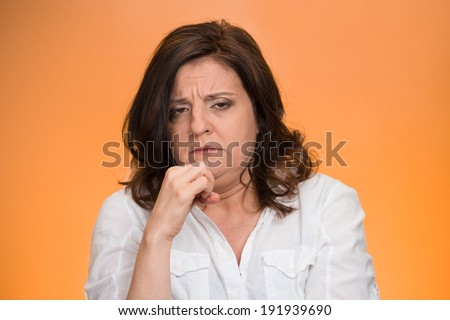 Closeup portrait displeased, pissed off, angry, grumpy, middle aged woman with bad attitude, hand on chin looking at you, isolated orange background . Negative human emotion facial expression feeling - stock photo
