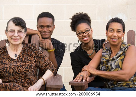 Closeup portrait, diverse, smiling, multigenerational family sitting down, isolated outside background - stock photo