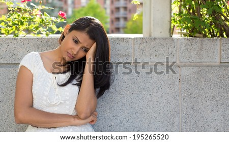 Closeup portrait, dull upset sad young woman in white dress sitting on bench, really depressed, down about something, isolated gray background. Negative emotion facial expression feeling body language - stock photo
