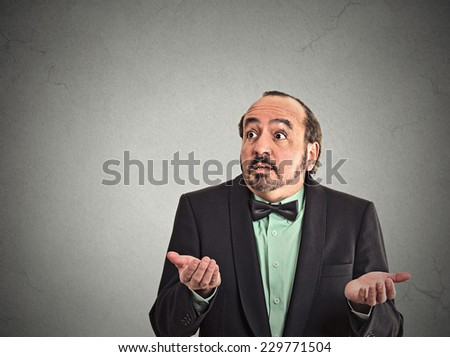 Closeup portrait dumb clueless middle age man arms out asking what's the problem who cares so what I don't know isolated on grey wall background space to left. Negative human emotion facial expression - stock photo