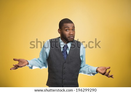 Closeup portrait dumb looking, clueless business man, arms out asking why, what's problem, so what, I don't know, isolated yellow background. Negative human emotion facial expression, life perception - stock photo