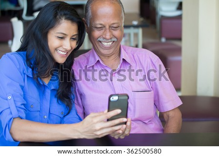 Closeup portrait elderly gentleman in pink shirt and lady in blue top family enjoying mobile phone fun, isolated indoors background - stock photo