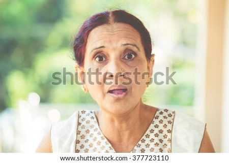 Closeup portrait, elderly woman in white dress taken aback, blown away, by what she sees or hears, isolated outdoors outside background with green trees - stock photo