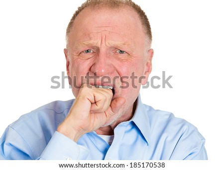Closeup portrait, employee worker, senior mature man person looking at you and biting fist in neurotic nervous manner, isolated white background. Negative human emotion facial expressions feelings. - stock photo