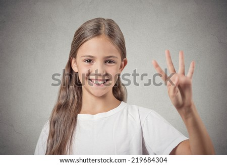 Closeup portrait excited happy teenager girl showing 4 fingers, giving number four sign isolated grey wall background. Positive emotion face expressions, feelings, attitude, perception body language - stock photo